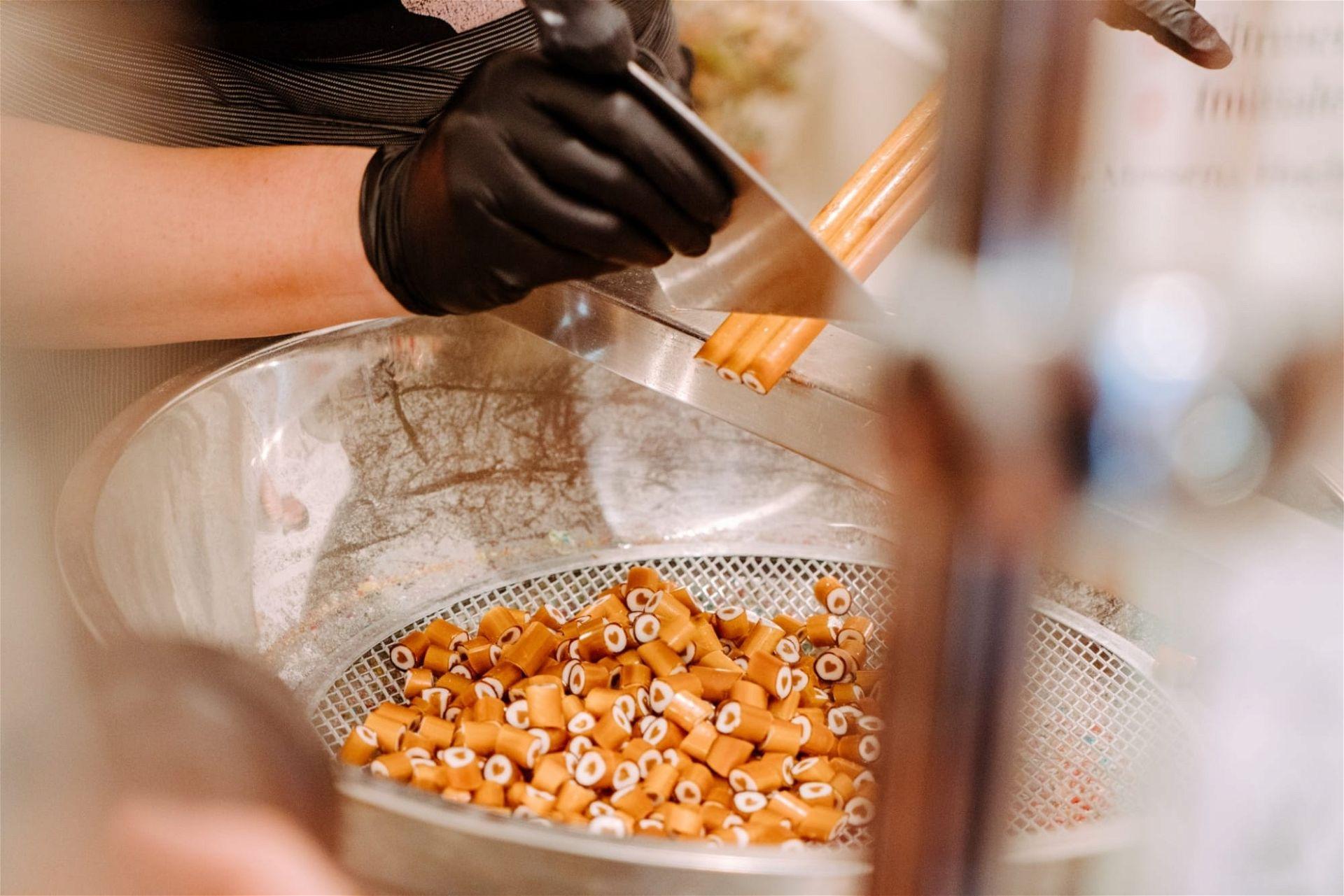 Als letzten Schritt in der Herstellung werden aus den langen Stangen einzelne Zuckerl abegschnitten - (c) Ines Futterknecht